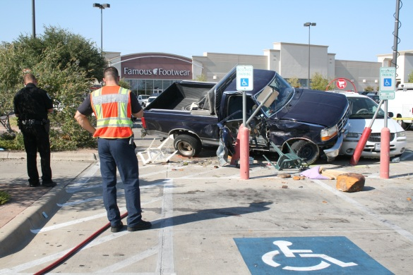 Police survey the accident site where the out of control truck landed on top of two vehicles in the parking lot.