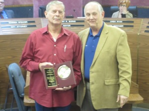 Mayor Jerry Burns presents a plaque of appreciation for service on the council to Paul Moore.