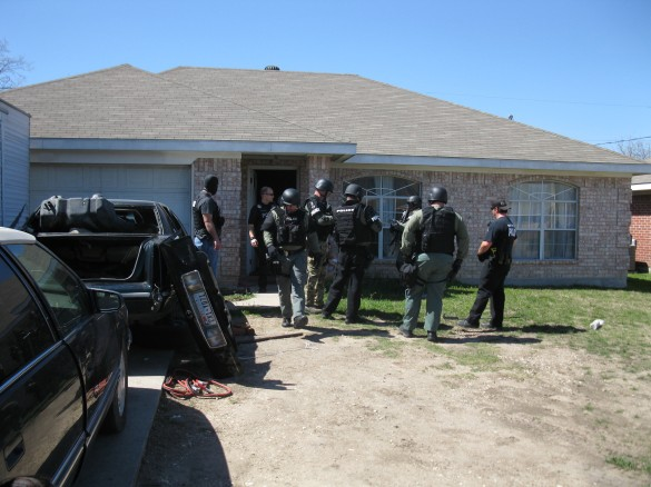White Settlement Police Officers discuss the situation after securing the home on Las Vegas Trail.