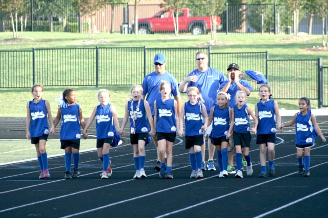 The White Settlement Youth Association Pinto 8U team walks with their coaches before hundreds of spectators at BHS stadium.