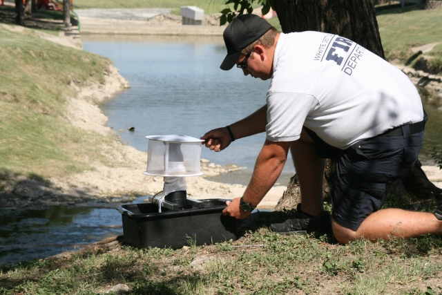 WS Firefighter Brady Graham sets up a mosquito trap near a creek to collect mosquitoes to be tested.