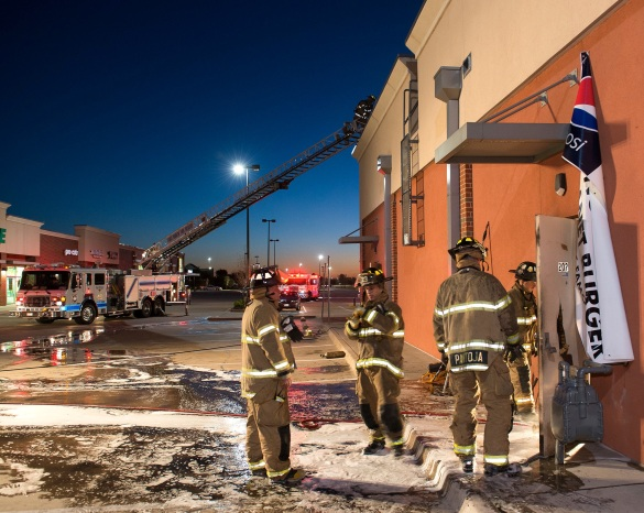 Firefighters crawl onto the roof of the building from their ladder truck as others enter through the back door of Planet Burger to check for hot spots. Photo by Glen Ellman/FWFD