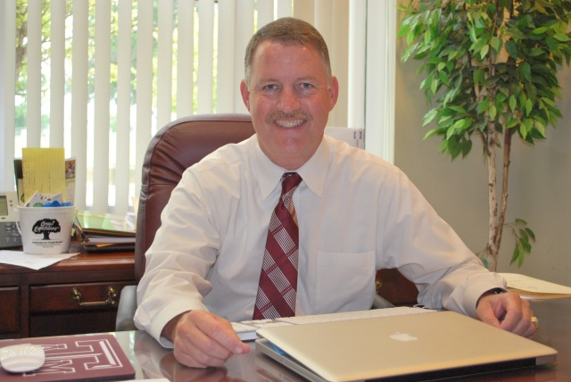 John Hebert working at his desk as Asst. Super-intendent of Curriculum, Instruction & Admin. Services for the White Settlement ISD.