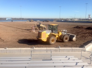Construction workers preparing the ground for the new artificial turf on the baseball field.
