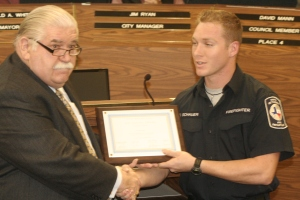 Firefighter Dusty Schauer is presented a certificate by Mayor Ron White.