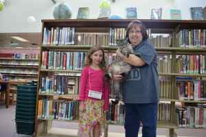 Claire Smith poses with Browser the cat and a library worker.